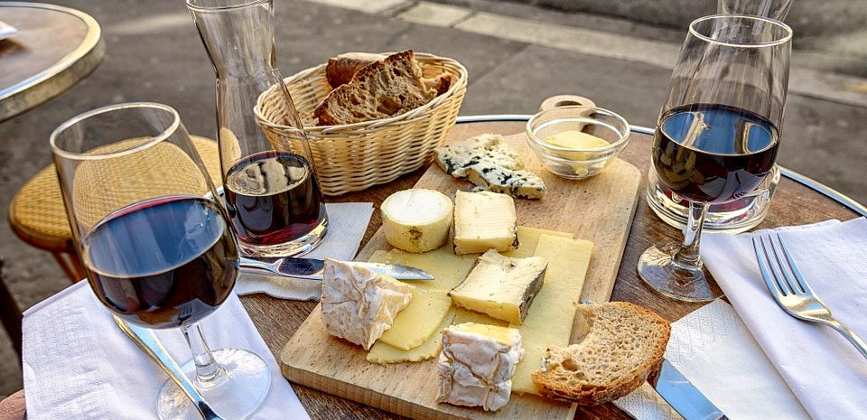 A table laid out with a selection of cheeses and a carafe of wine