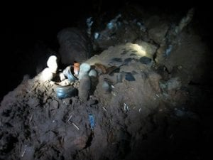 flashlight illuminating relics in a mayan cave
