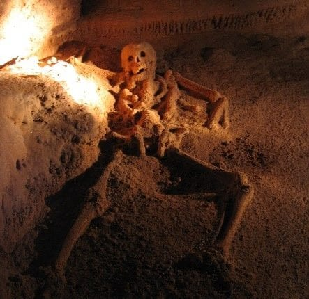 a skeleton splayed out on the floor of a mayan cave