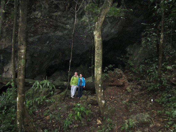 tourists at the mouth of a cave in Belize