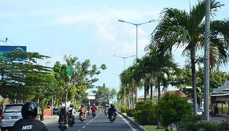 motorcycles and cars on a bust street in bali Indonesia