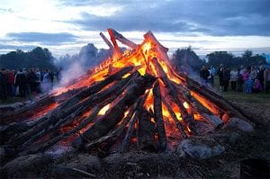a bonfire burning in front of a crowd of people