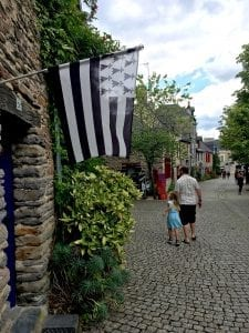 A Black and White Brittany flag hangs on a stone building