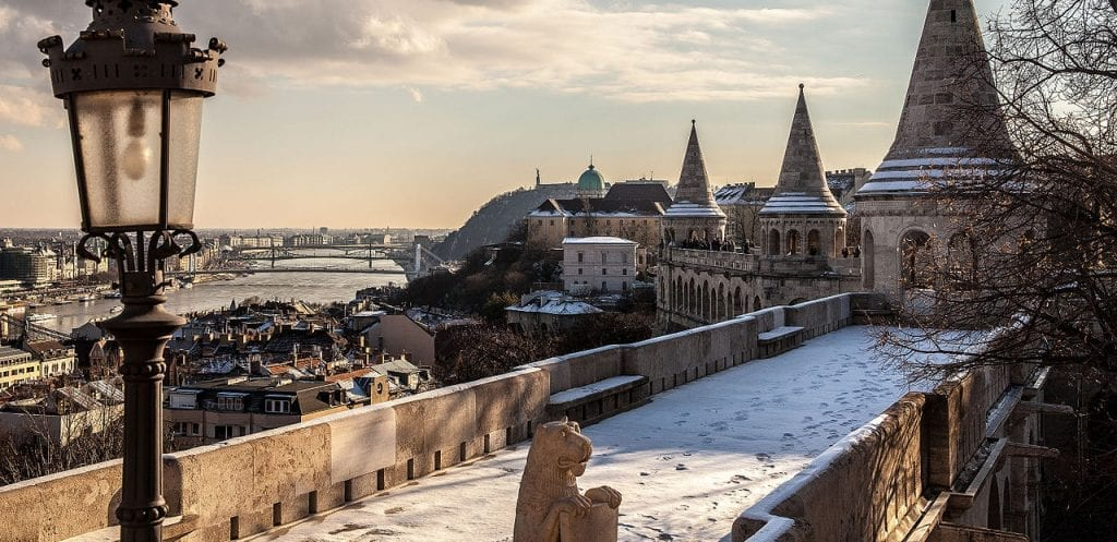 a snow covered bridge overlooking the beautiful Budapest architecture