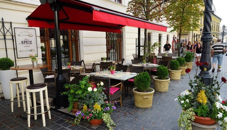An outdoor cafe with red awnings in Budapest