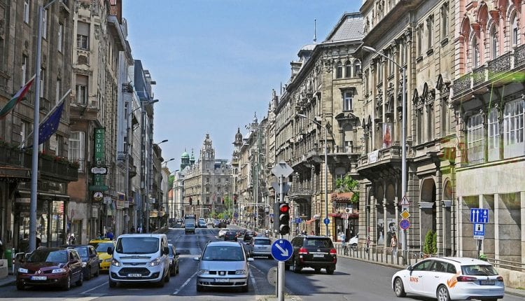 cars driving down a busy street in Budapest-s Historic Center