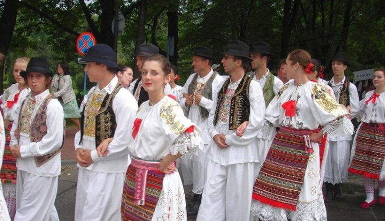 Men and women dressed in typical white attire with colorful belts and vests
