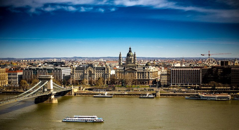 a ferry navigates the danube in front of the parliament in budapest