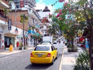 a taxi drives up a beautiful street lined with shops and bougainvillea