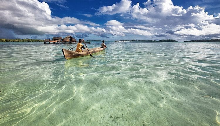wooden boats rowing away from an Indonesian beach