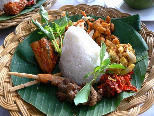 a typical Indonesian plate with rish and vegetables and chicken