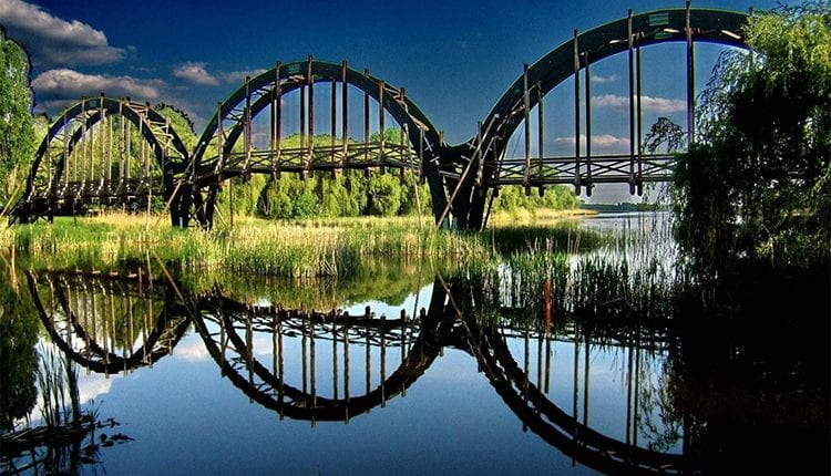 a bridge made up of repeating half moons that look like circles with the reflection in the water