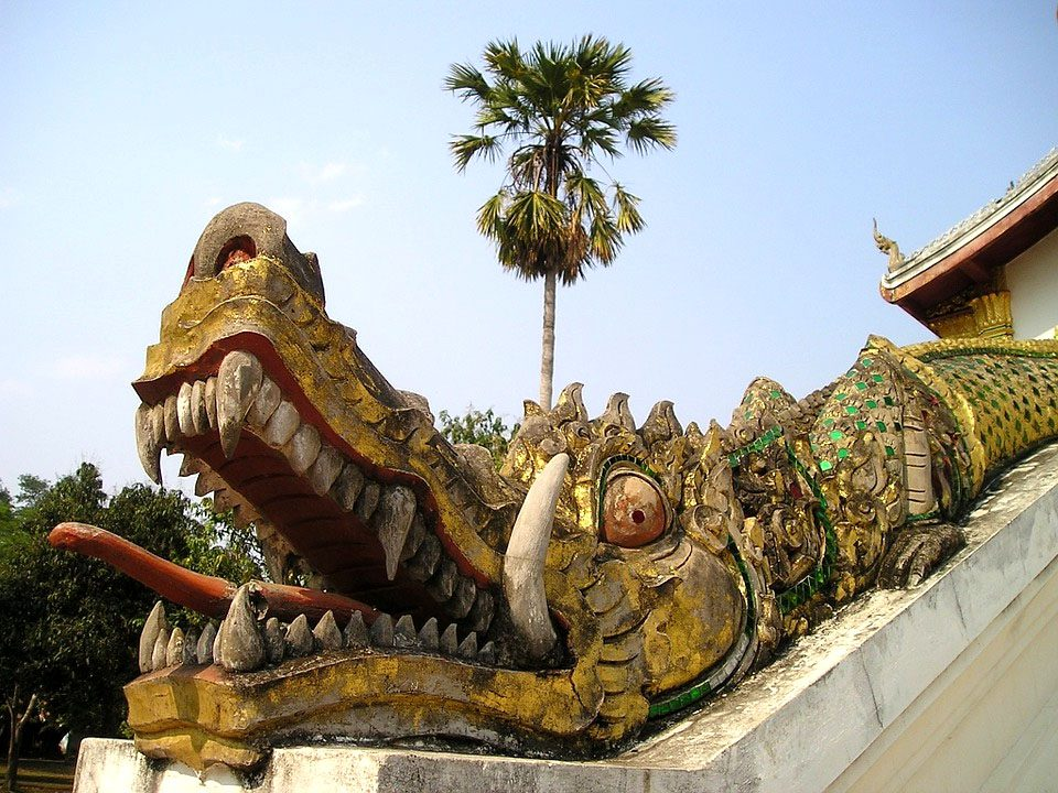 an elaborate dragon on temple stairs in Laos