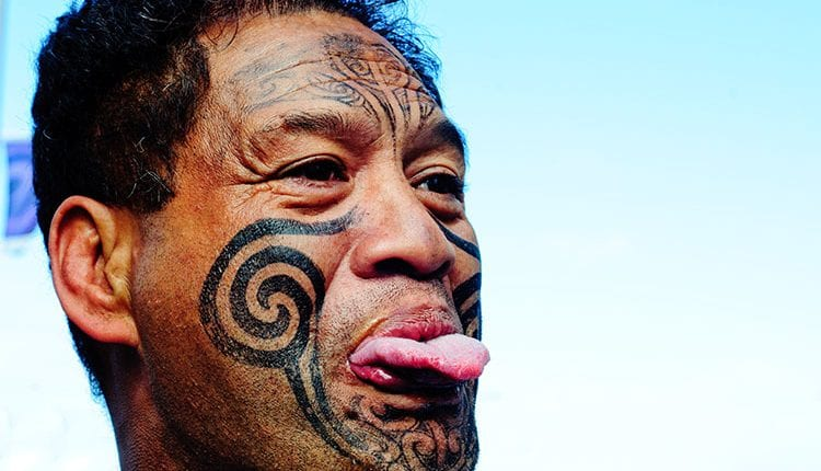 a tattoed maori man sticking out his tongue