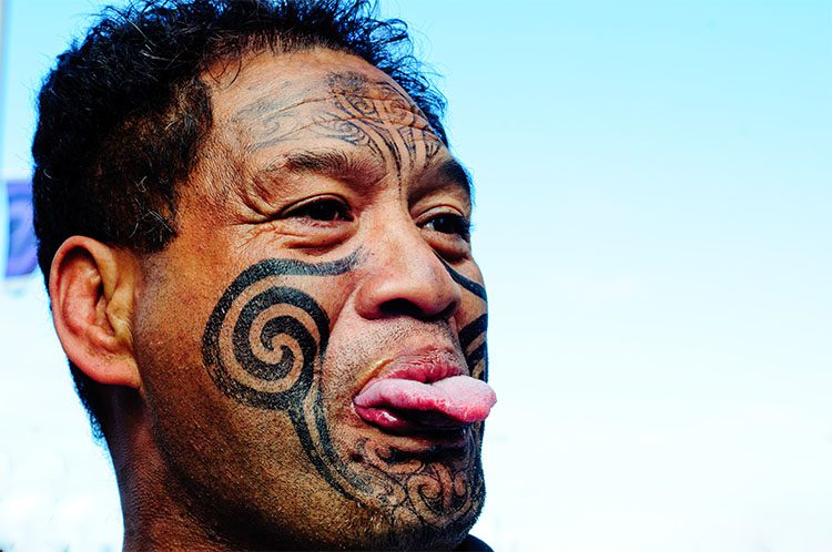 a tattoed maori man sticking out his tongue