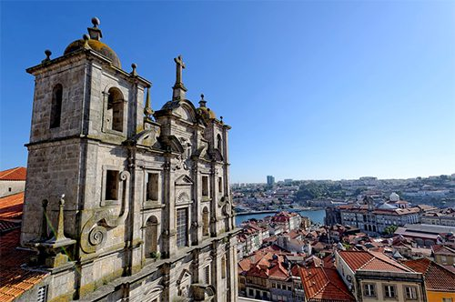 a beautiful old church and rooftops next to the ocean in Portugal