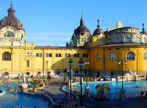 people enjoying a yellow public bath house with large pools