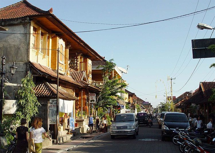 a street in bali indonesia with cars and people