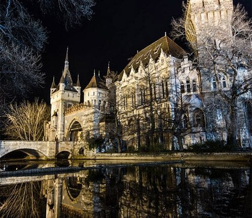 night view of Vajdahunyad Castle and its reflection in water