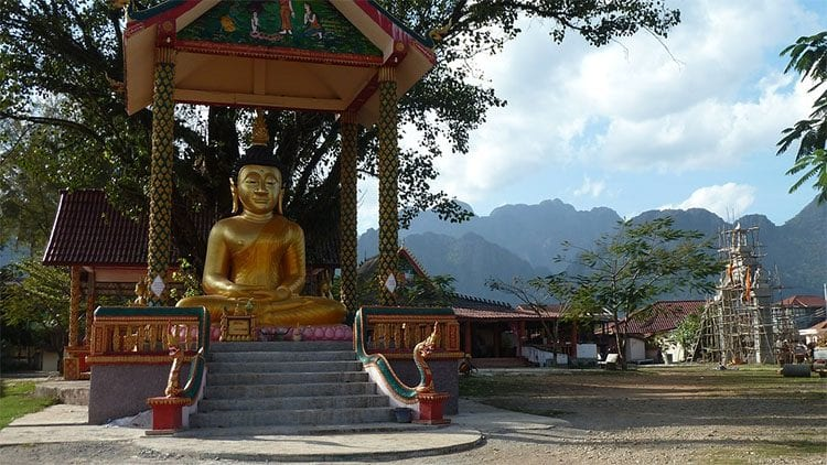 a gold Buddhist statue under a roof in VangVieng Laos