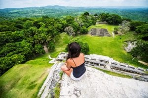 Woman sits on the edge of a Mayan ruin