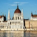The very large parliament buildign by the Danube river glows in the light of the setting sun