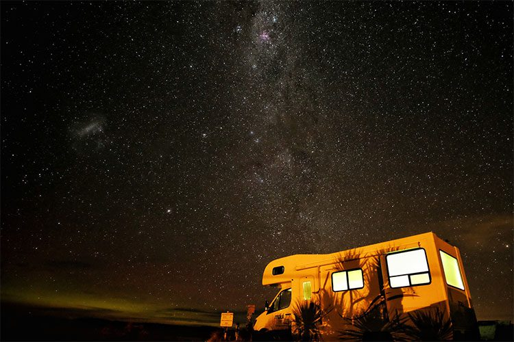 a camper parked under the night sky filled with stars