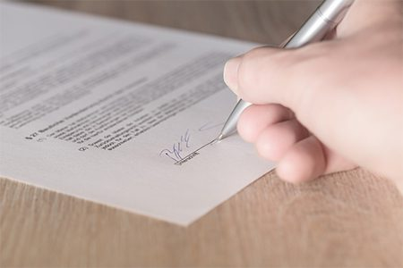 closeup of someone signing a contract
