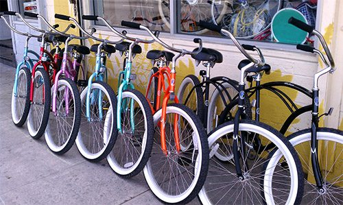 A row of colorful bicycles leaning on a storefront