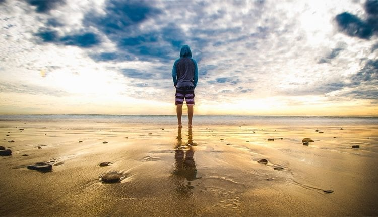 man in shorts and a hooded shirt standing on beach looking at the ocean