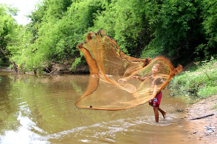 a boy casts his net for fishing in a riverin Laos