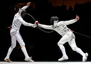 Two athletes dressed in white fencing in a competition