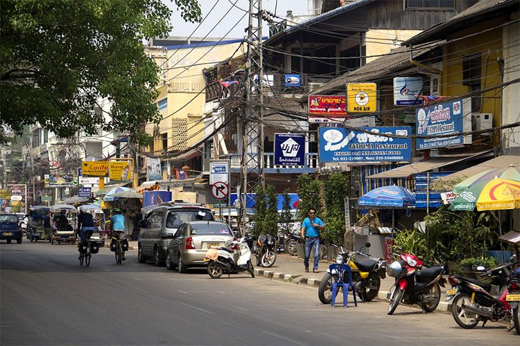 a busy street lined with shops in Laos