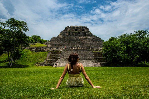 A woman sitting in front of Mayan ruins