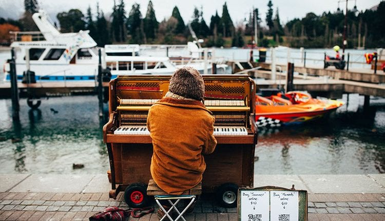 bundled up man playing piano outside on the docs
