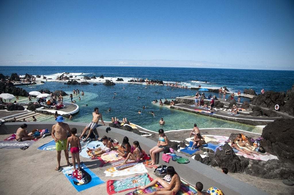 people swimming and lounging by the rock pools of porto moniz