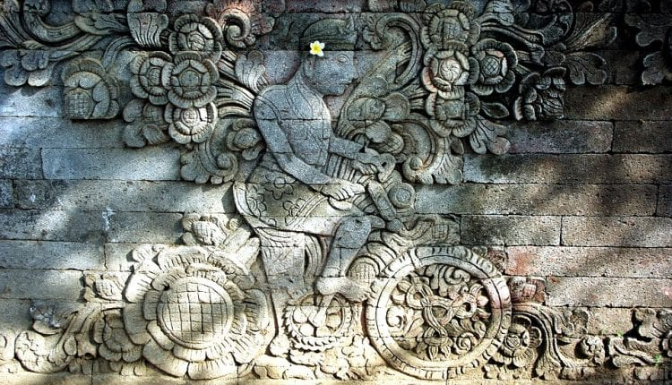 a stone wall with indonesian design carved into it