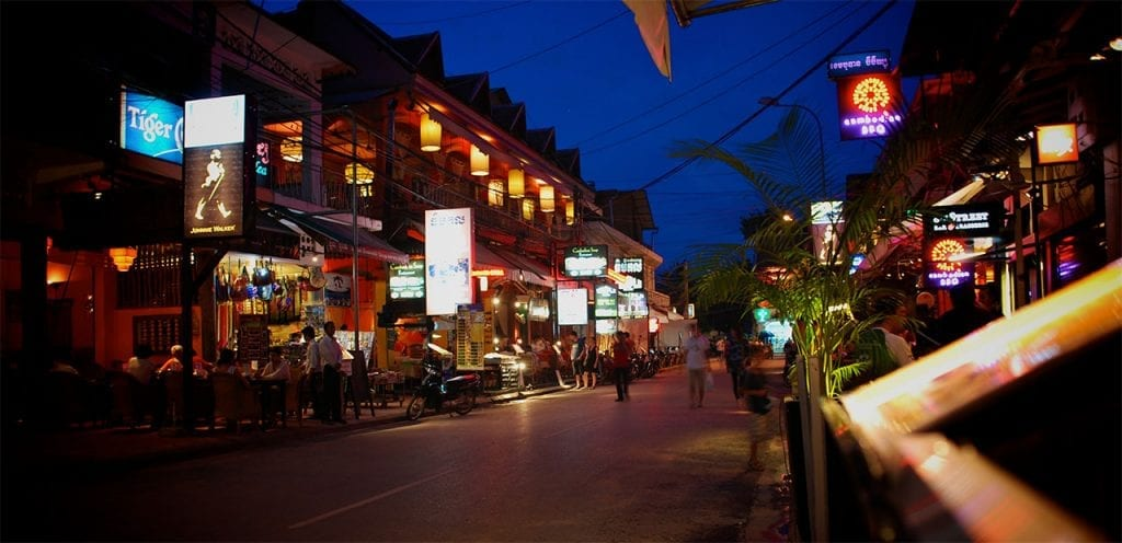 a siam reap street lined with shops lit up at night
