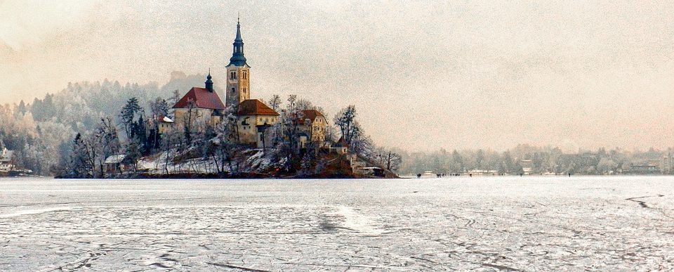 a small island with a church covered in show and surrounded by a lake frozen into ice