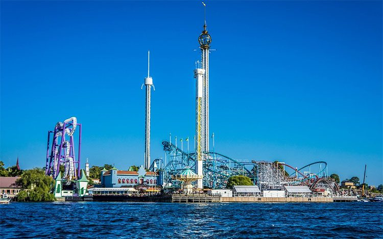 an amusement park with large roller coasters by the sea