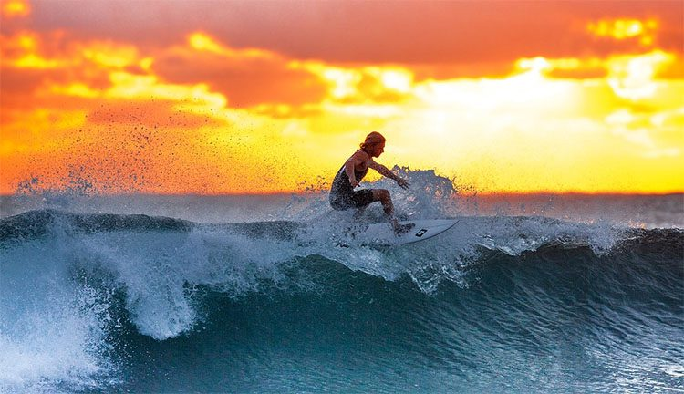 a srufer riding a wave at sunset in Indonesia
