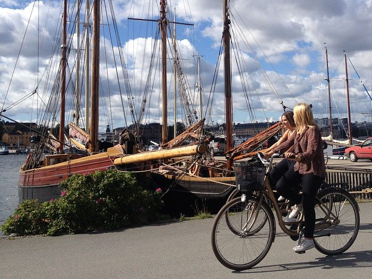 wooden boats docked in Sweden with two young women driving by on a bicycle