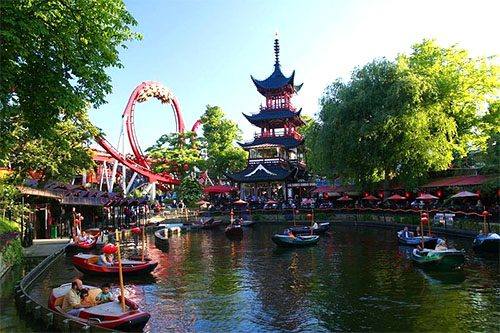 an asian structure, a roller coaster and small boats in a pond at Tivoli Gardens