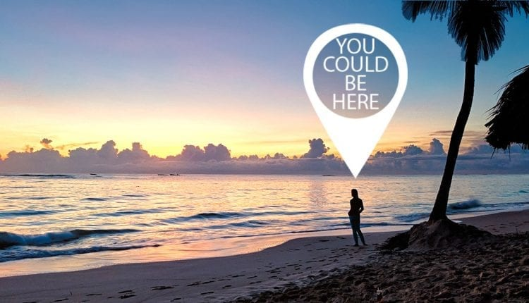 a woman silhouetted on a beach with a sign that says you could be here above her head
