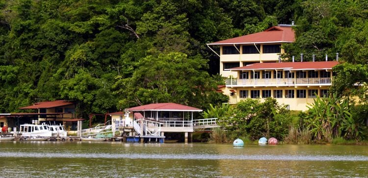 Buildings and dock on the water's edge in Barro Colorado Panama. Green reain forest in the back.