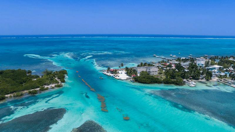 aerial view of cristaline water between belize rental market . English is spoken throughout Belize along with the native languages.