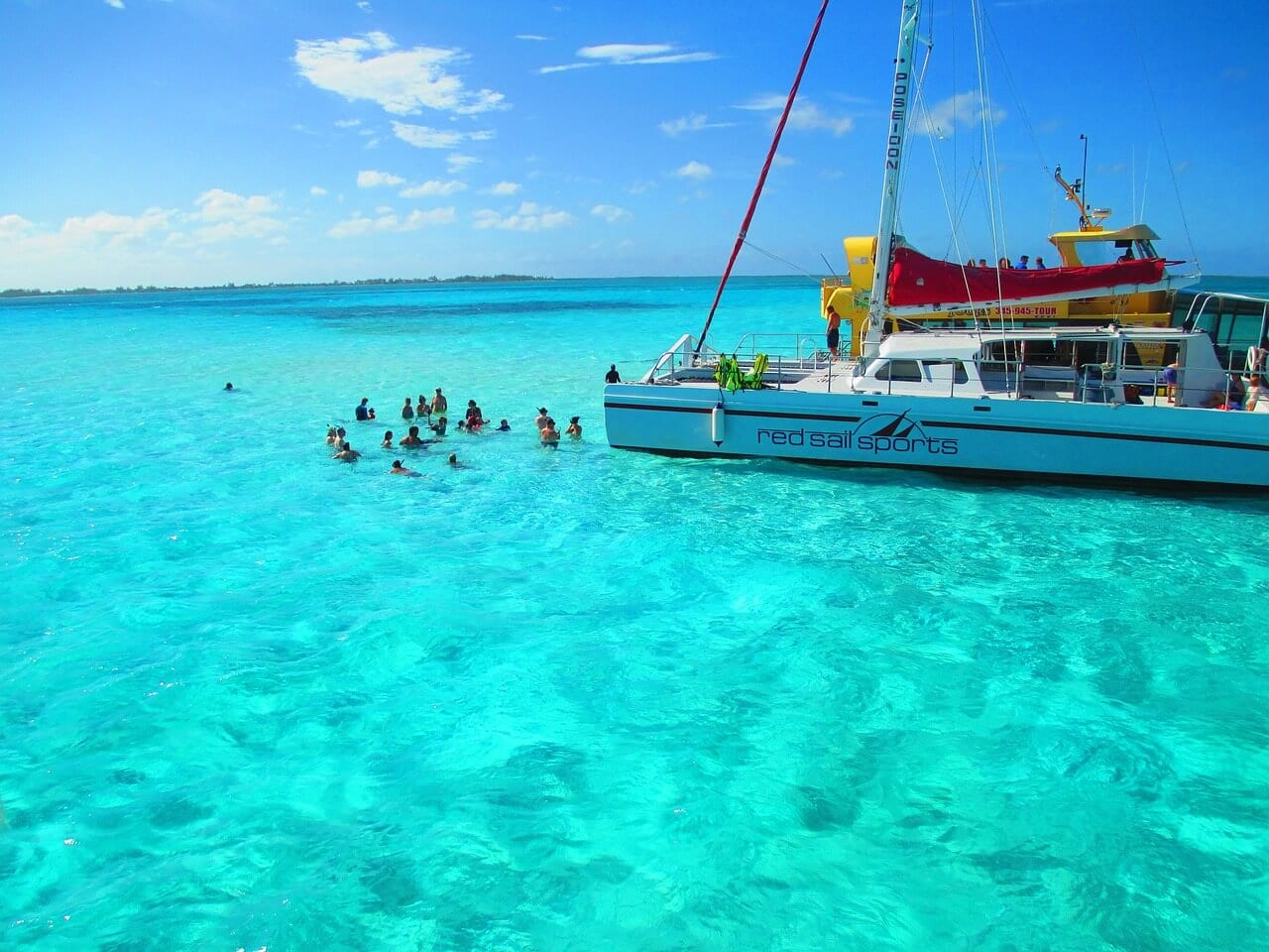 A boat and people sitting in the crystal clear blue water off the shores of the Cayman Islands
