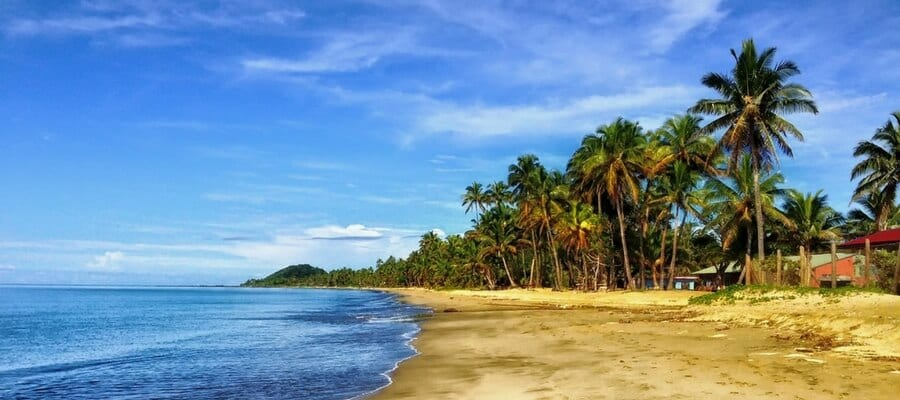 A calm and remote beachfront in Fiji, with palm trees swaying in the background.