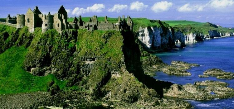 A view of the gorgeous green cliffs on the shore of Ireland with old stone structures sitting just on the plateau.