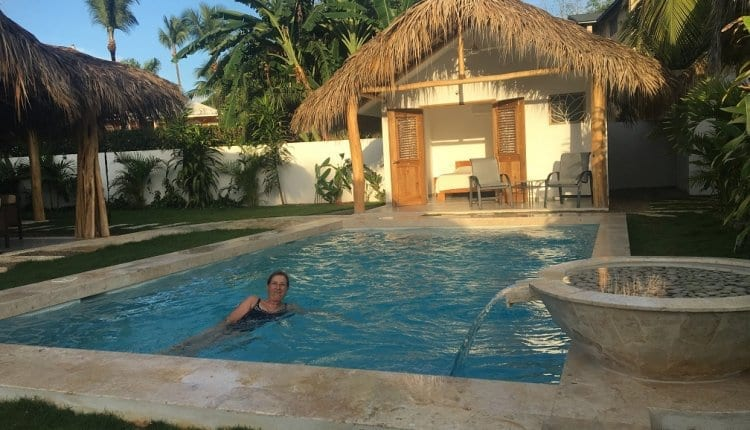 Woman swimming in a pool behind her tropical home.